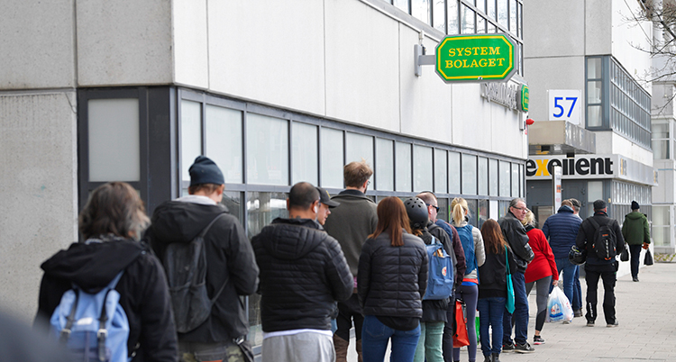 Människor står i en kö på trottoaren utanför Systembolaget