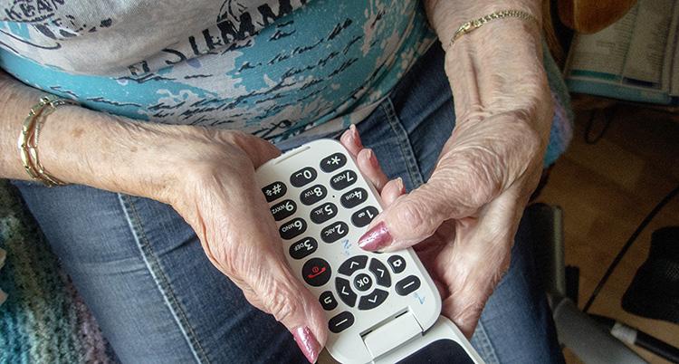 En kvinna trycker på knappar på telefonen.