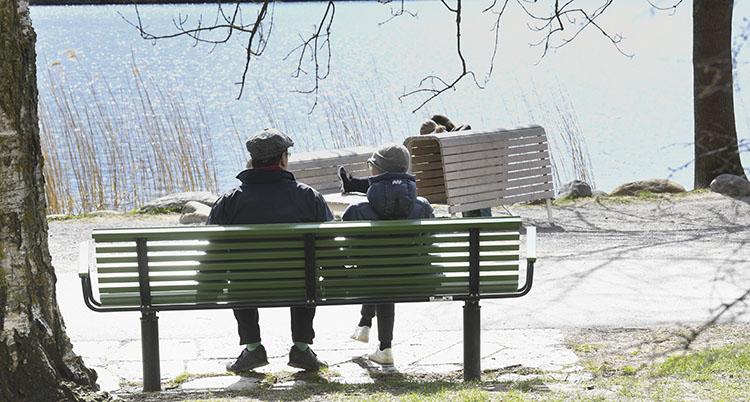 Två personer sitter på en bänk. Solen skiner.