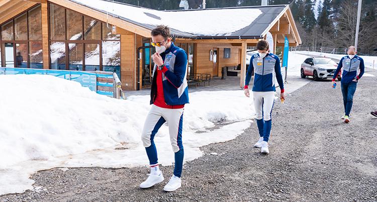 Två åkare utan skidor går på en grusväg. Bredvid dem är det mycket snö. Men det syns att det smälter. Ingen av åkarna har mössa eller vantar.