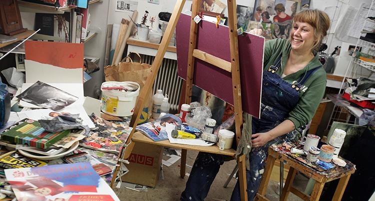 Hon sitter i sin ateljé och målar en tavla.