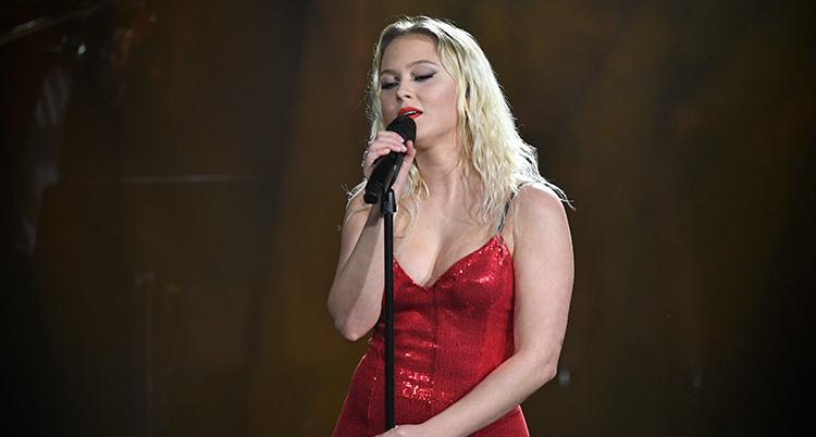 Hon har en röd glittrig klänning och står vid en mikrofon och sjunger