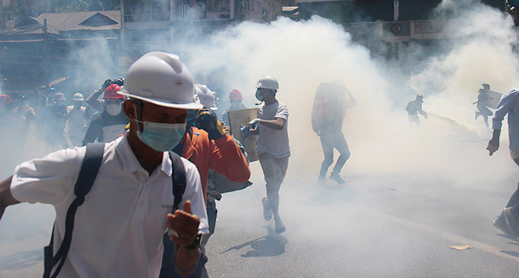 Bilden är tagen på en gata i Myanmar. Det är rök och gas på gatan. Människor springer från den. Personen närmast kameran har hjälm och munskydd.