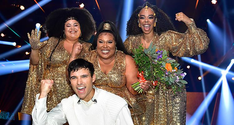 Alla fyra är glada. De tittar in i kameran. The Mamas är tre kvinnor. De står längst bak. Framför dem sitter Eric Saade.
