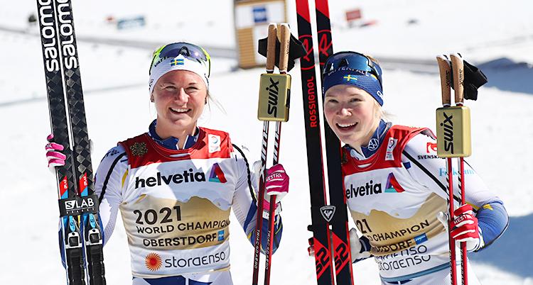De har precis vunnit loppet. De är glada. De står och håller i sina skidor och stavar.