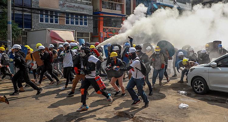 Vi ser en gata i staden Rangoon. En grupp med människor springer bort från ett stort moln. Molnet är tårgas. Människorna har på sig hjälmar och skyddsglasögon.