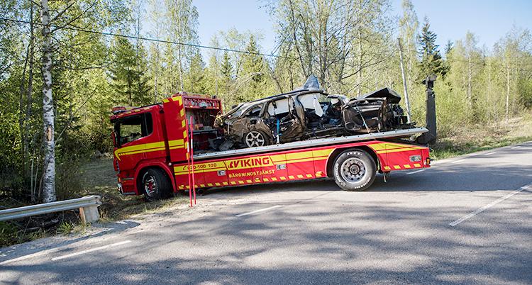 Bilden visar en landsväg. Det finns skog bredvid vägen. Himlen är blå. En röd bärgningsvbil håller på att backa upp på vägen. På flaket finns en personbil som är mycket skadad.