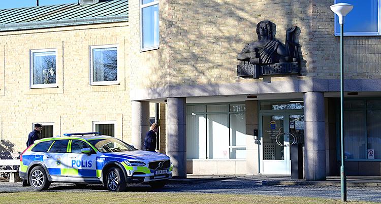Bilden visar en byggnad. Utanför står en polisbil.