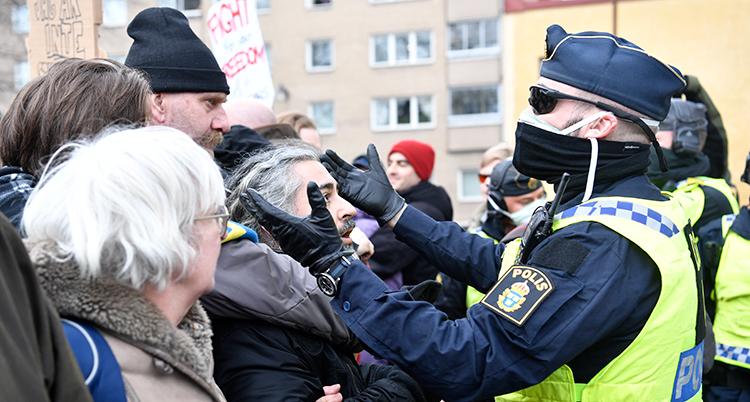 poliser med munskydd framför människor som trängs.