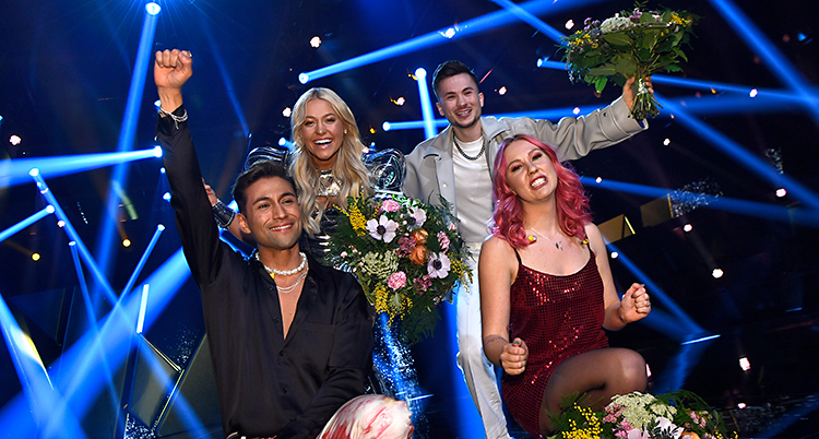 Det är fyra glada personer på bilden. De står på en scen. Det är blå strålkastare i bakgrunden.