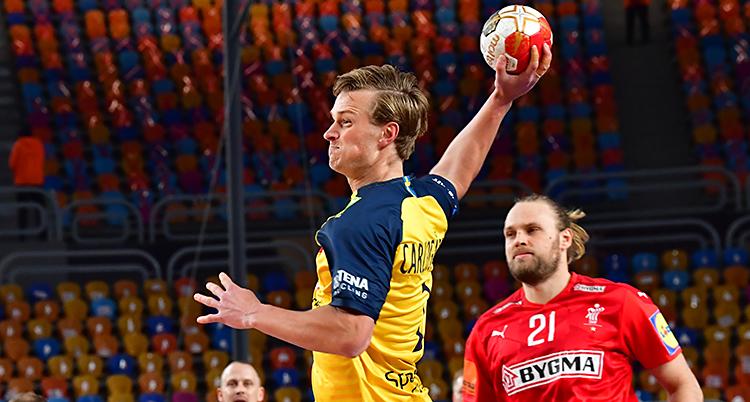En match i handboll. En spelare i Sveriges lag håller i bollen. Han är på väg att skjuta. Han har gul tröja. Det andra laget har röda tröjor.
