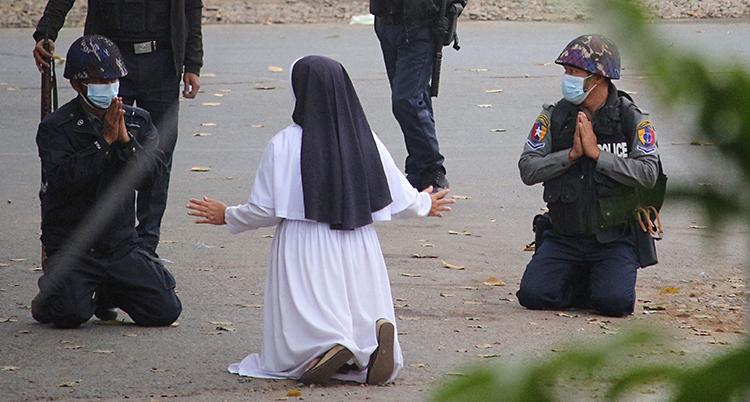En nunna står på knä på marken. Vi ser henne bakifrån. Framför henne är fyra poliser. Två av poliser står också på knä.
