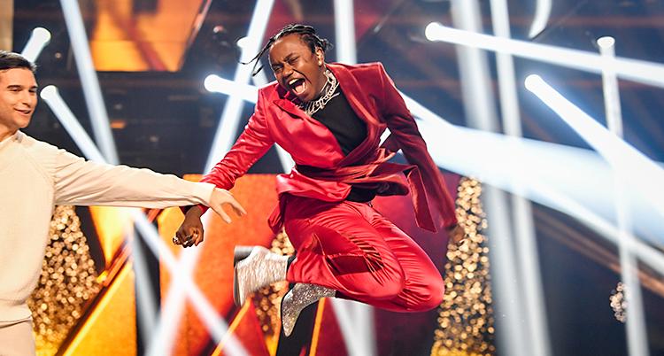 Bilden visar scenen i Melodifestivalen. Det är massor av strålkastare på scenen. Artisten Tusse har precis fått veta att han vunnit. Han hoppar upp i luften och skriker av glädje. Han har en röd kostym. Till vänster om Tusse står Eric Saade.