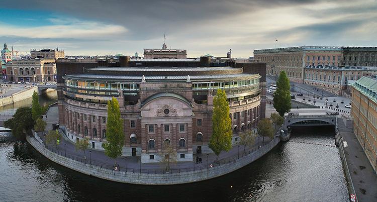 en bild ovanifrån på riksdagens byggnad. Omgiven av vatten och en vackert molnbeslöjad himmel.