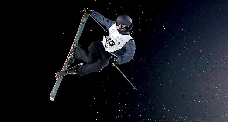 Oliwer Magnusson hoppar med skidor. Han är i luften. Han gör ett trick med skidorna. Han har svarta kläder och en svart hjälm.