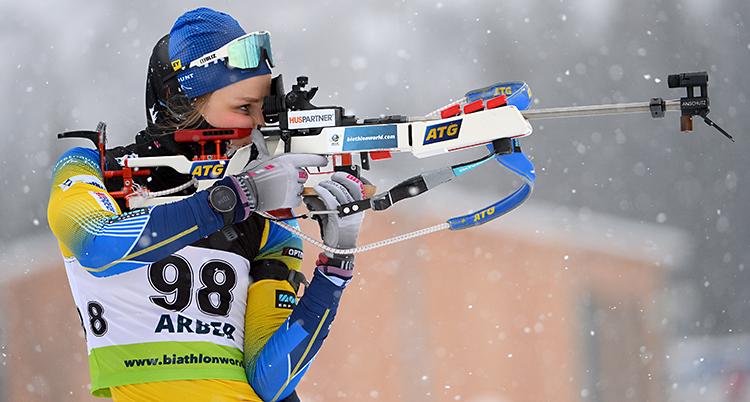 Stina Nilsson på en tävling. Hon siktar med sitt gevär. Hon har en gul och blå dräkt. Det snöar litegrann.