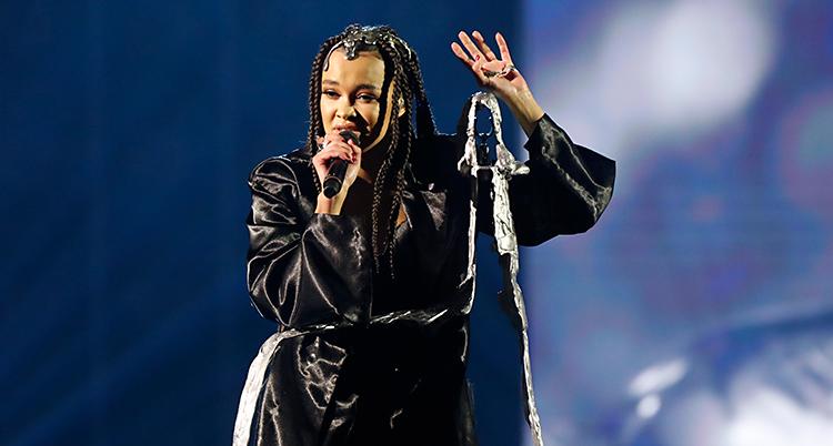 En kvinna sjunger på en scen. Hon har en mikrofon. Hon har svarta kläder och små flätor i håret.