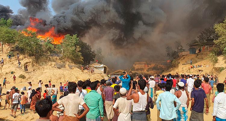 människor tittar på en stor eld som brinner en bit bort.