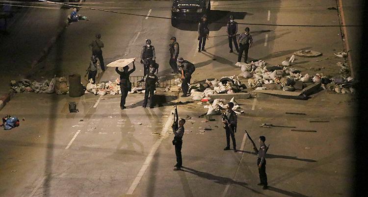 Det är kväll. Bilden är tagen uppifrån, ner mot en gata. Där finns ungefär tio poliser med vapen.