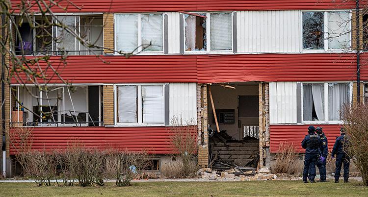 Bilden visar ett hus med lägenheter. Porten till huset har blivit skadat. Flera fönster har gått sönder. Några poliser står utanför huset.