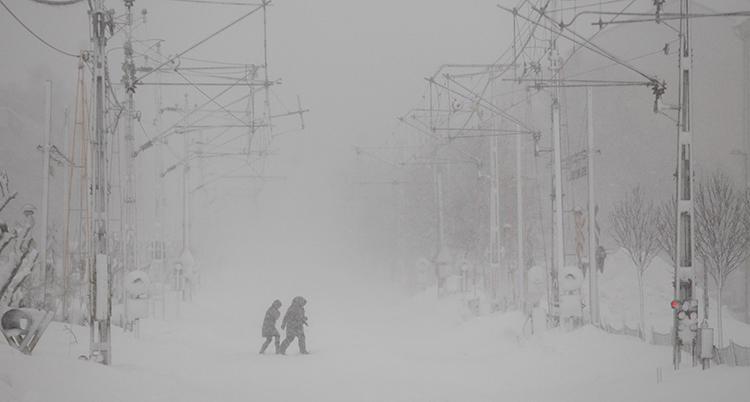 Bilden är tagen utomhus. Det blåser och snöar. Två personer går över ett järnvägsspår.