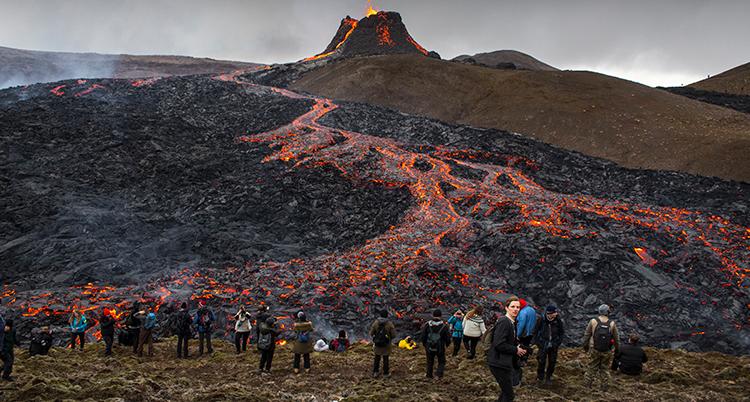 människor står på avstånd från vulkanen och tittar.