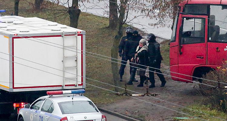 Tre poliser har tagit fast en kvinna. Poliserna har svarta kläder och masker för ansiktet. Runt dem ser vi några träd och några bilar.