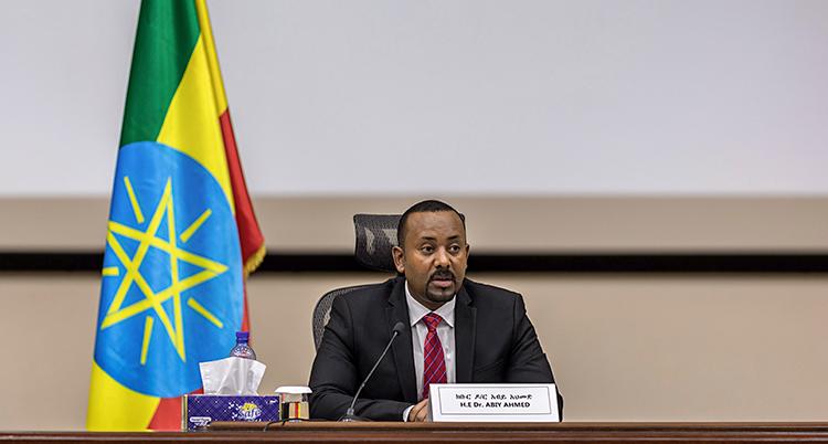 Abay Ahmed sitter vid ett skrivbord. Han pratar i en mikrofon. Han har kostym och slips. I bakgrunden är Etiopiens flagga.