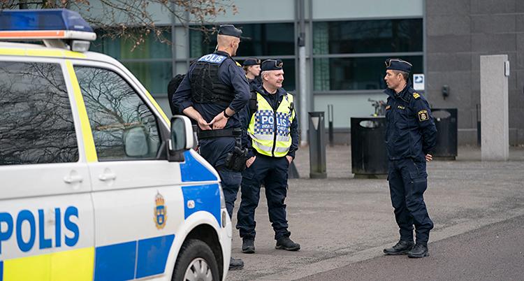 Tre poliser står och pratar med varandra. De står utanför en byggnad som är stor och grå. Bredvid poliserna är en polisbil.
