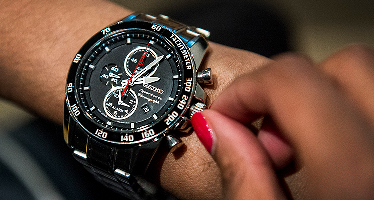 En klocka sitter på en arm. En hand med rött nagellack ändrar tiden på klockan.