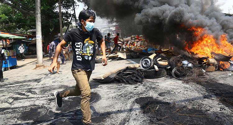 En ung pojke springer på en gata framför något som brinner.