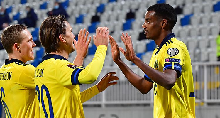 Bilden är från en match i fotboll. Tre spelare från Sverige firar ett mål. De har gula tröjor.