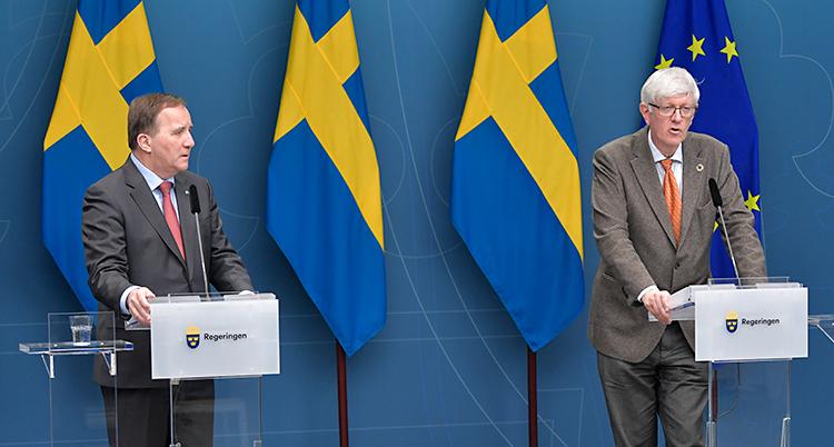 Löfven och Carlson står i ett blått rum. Bakom sig har de svenska flaggan och EUs flagga. De står vid varsitt litet bord och pratar i varsin mikrofon. De har kostym och slips.
