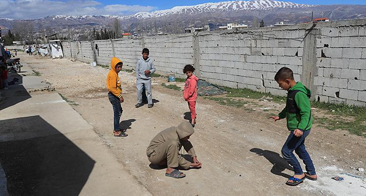 Fem barn leker på en grusväg. Bredvid dem är en mur. I bakgrunden syns berg med snö på topparna.