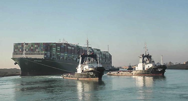 Bilden är tagen på Suezkanalen. Två små båtar kör mot kameran. De har linor som går från sina båtar till ett stort fartyg. På fartyget finns det massor av containrar.