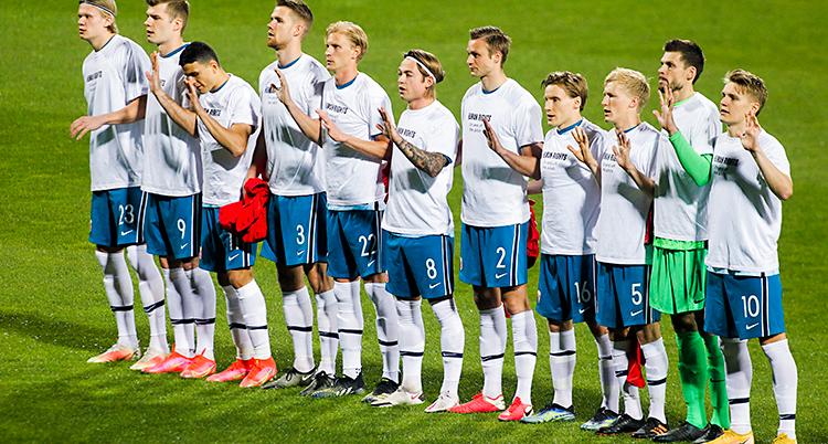 Norges lag står på en grön fotbollsplan. Spelarna står bredvid varandra. De har vita t-shirts med svart text på.