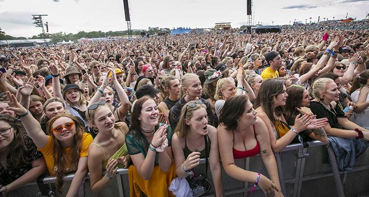 Massor av människor står tillsammans i en publik. De lyssnar på musik från en scen.