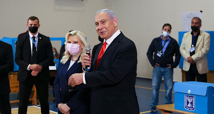 De står i en lokal där folk röstar. Hon har munskydd på sig. Det har inte han.