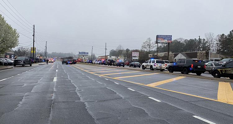 Flera polisbilar syns på en stora gata.
