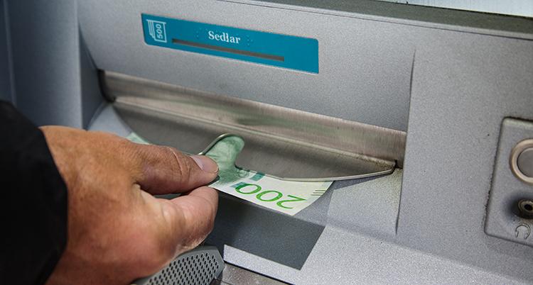 En hand tar emot en sedel som det står 200 kronor. Sedeln kommer ut ur en lucka.