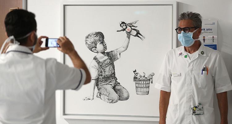 Vårdpersonal med munskydd står framför tavlan. På tavlan håller en pojke upp en docka som är en sjuksköterska.