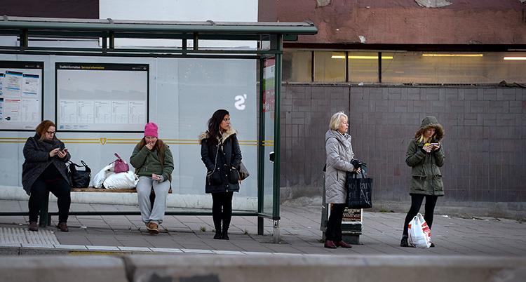 Folk väntar vid en busshållsplats. De står en bit ifrån varandra.