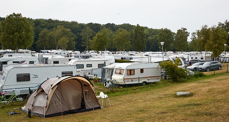 En campingplats full med husvagnar och ett tält längst fram i bilden.