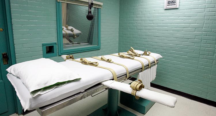 En brist med vita lakan och spännband står mitt på golvet i en cell med ett fönster