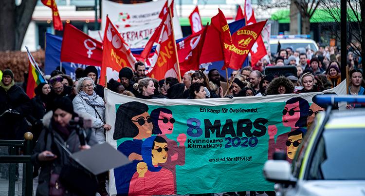 De går i ett demonstrationståg med flaggor och banderoller.
