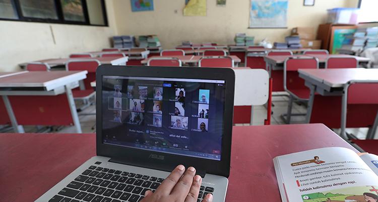 En datorskärm med många bilder på elever syns. I bakgrunden syns tomma bord och stolar.