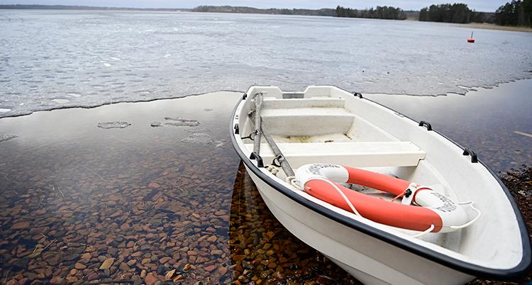 En båt ligger på en strand. I den ligger en livboj. Bakom en sjö med is. Men vid kanten syns det att isen är mycket tunn.