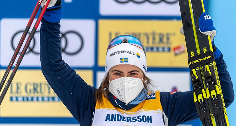 En närbild på Andersson. Hon hållert upp skidor och stavar. Hon ser glad ut trots att hon har munskydd. Hon har vir mössa och blå jacka. På hennes nummerlapp står det Andersson.