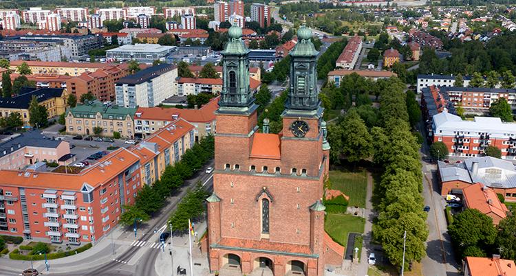 En översiktsvy över Eskilstuna, med Klosters kyrka i förgrunden och många hus bakom.