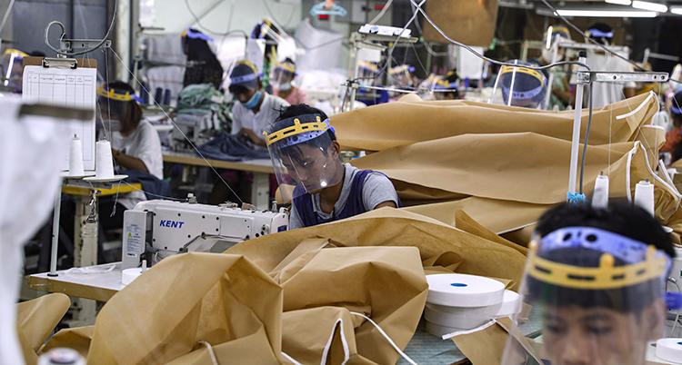 Två personer jobbar i en fabrik, de har visir.